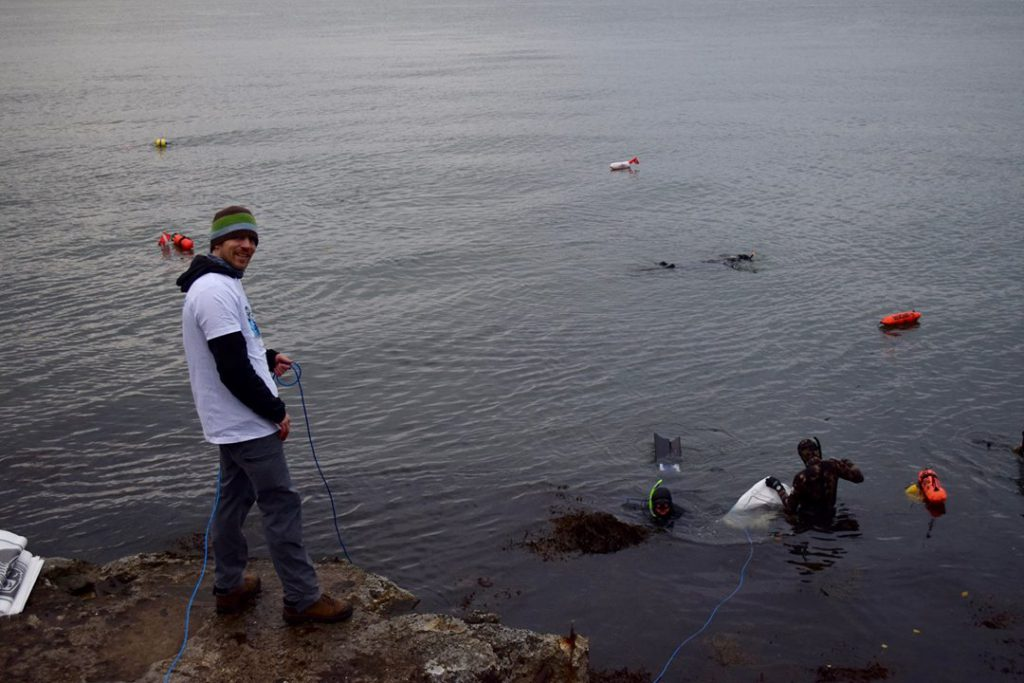 Bilde av person som står på land og tar i mot søppel fra fridykkere som rydder i havet.